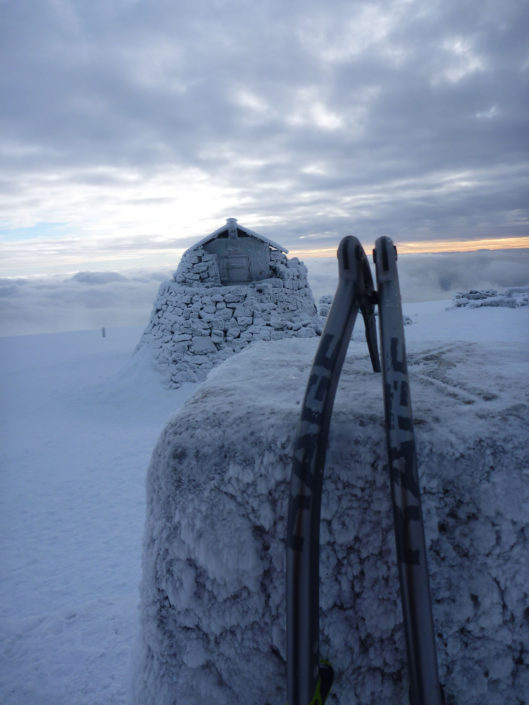Ice axes on the summit cairn of Ben Nevis